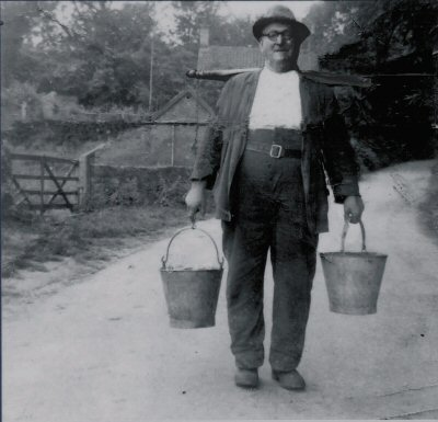 Prcy Whitworth taking the slops to the pigs in buckets hanging from a yoke.